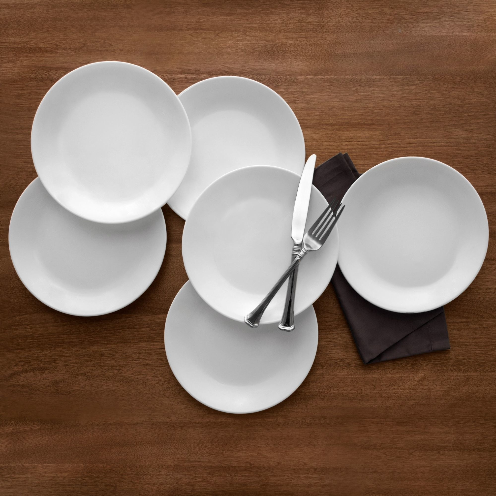 six white dinner plates on a table with a fork and knife on top
