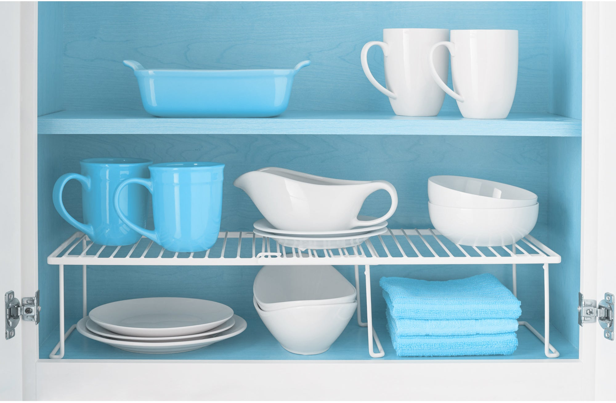 white expandable cabinet shelf with cups and bowls on top and plates underneath