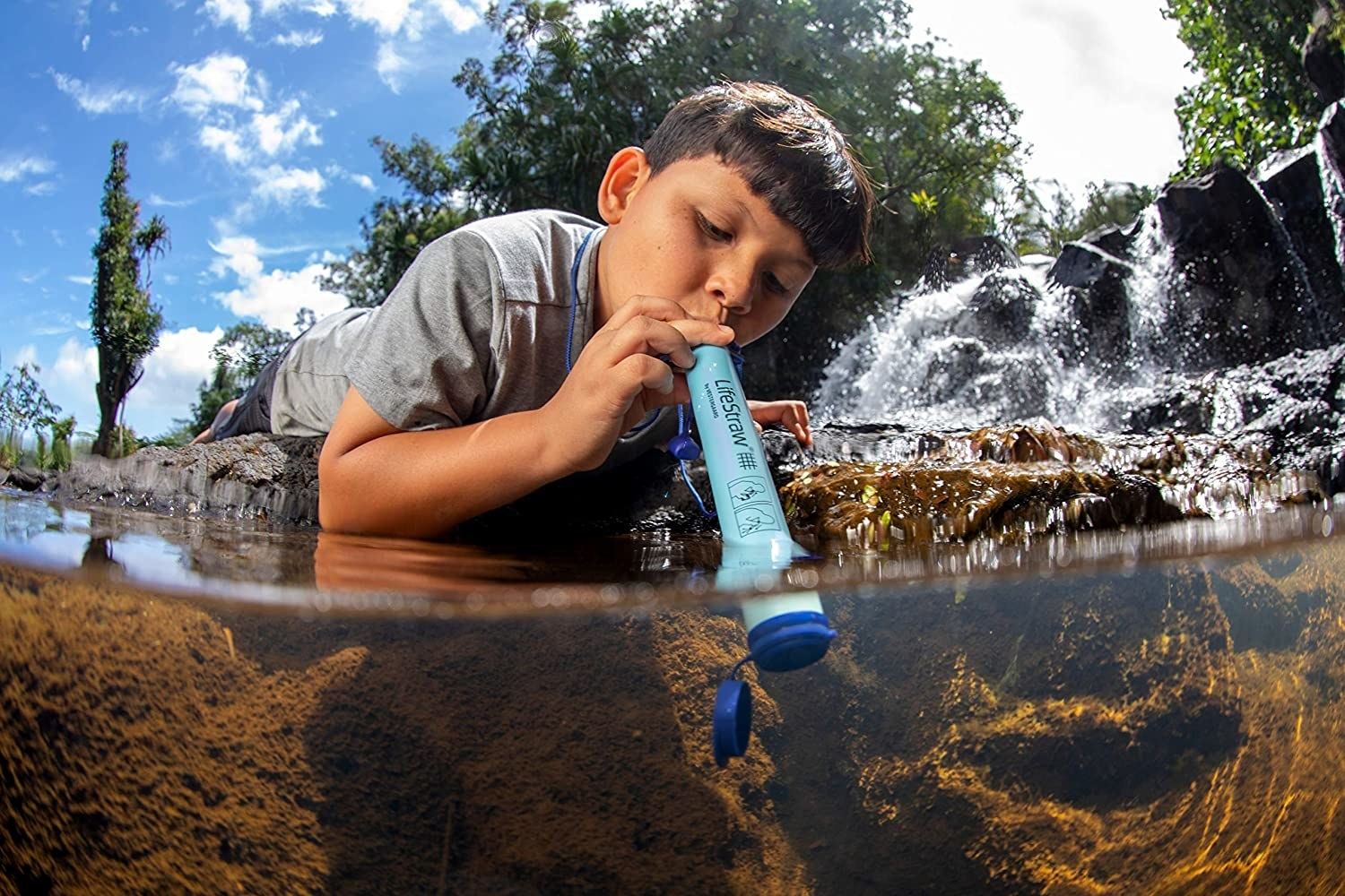 A person drinking straight from a river using the purifier.