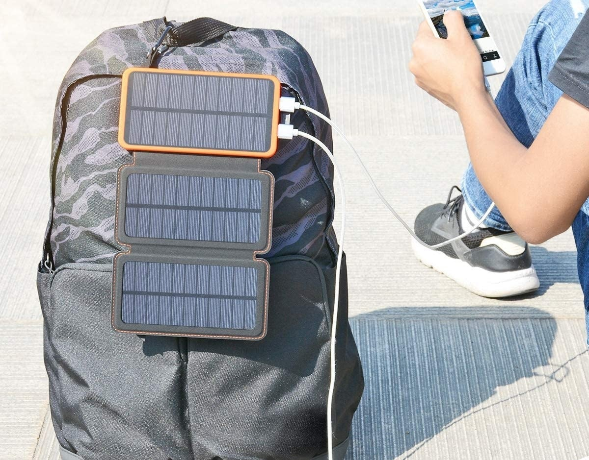 A person charging their devices under the sunlight.