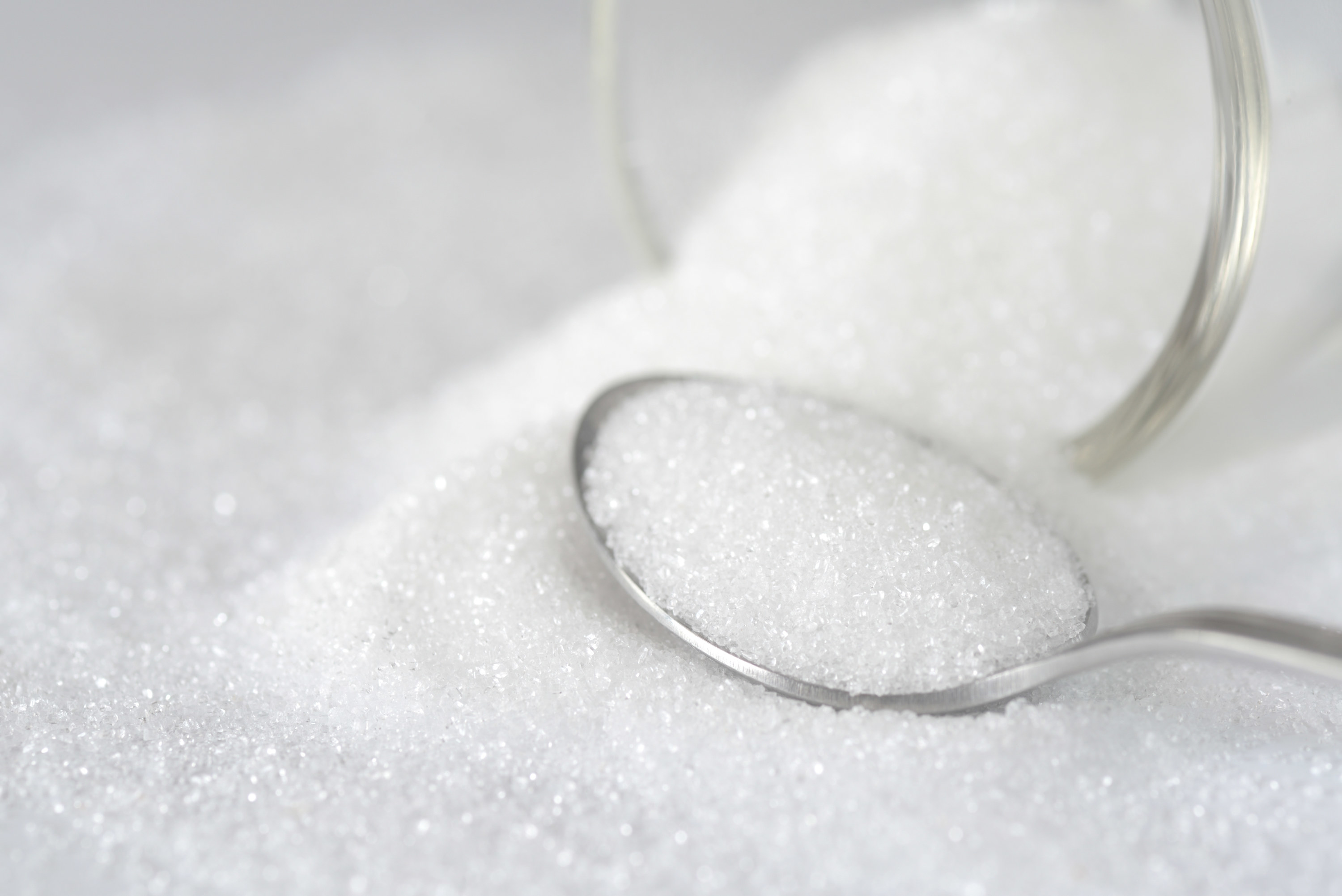 Spilled white sugar in a spoon