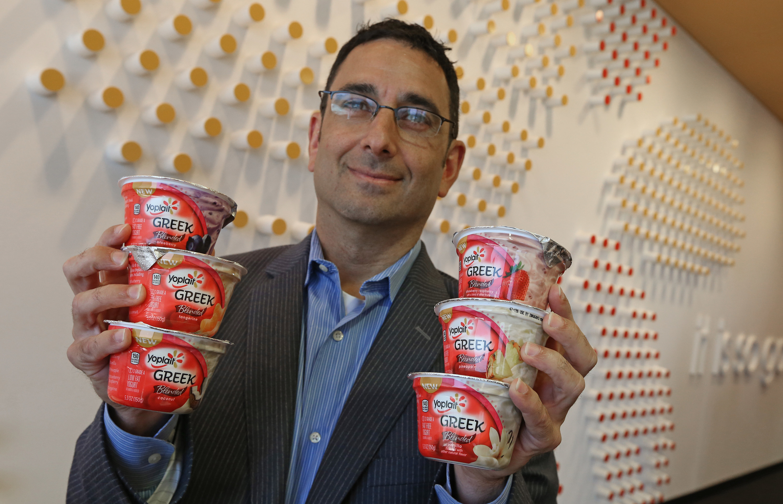 Man holding containers of Yoplait Greek yogurt