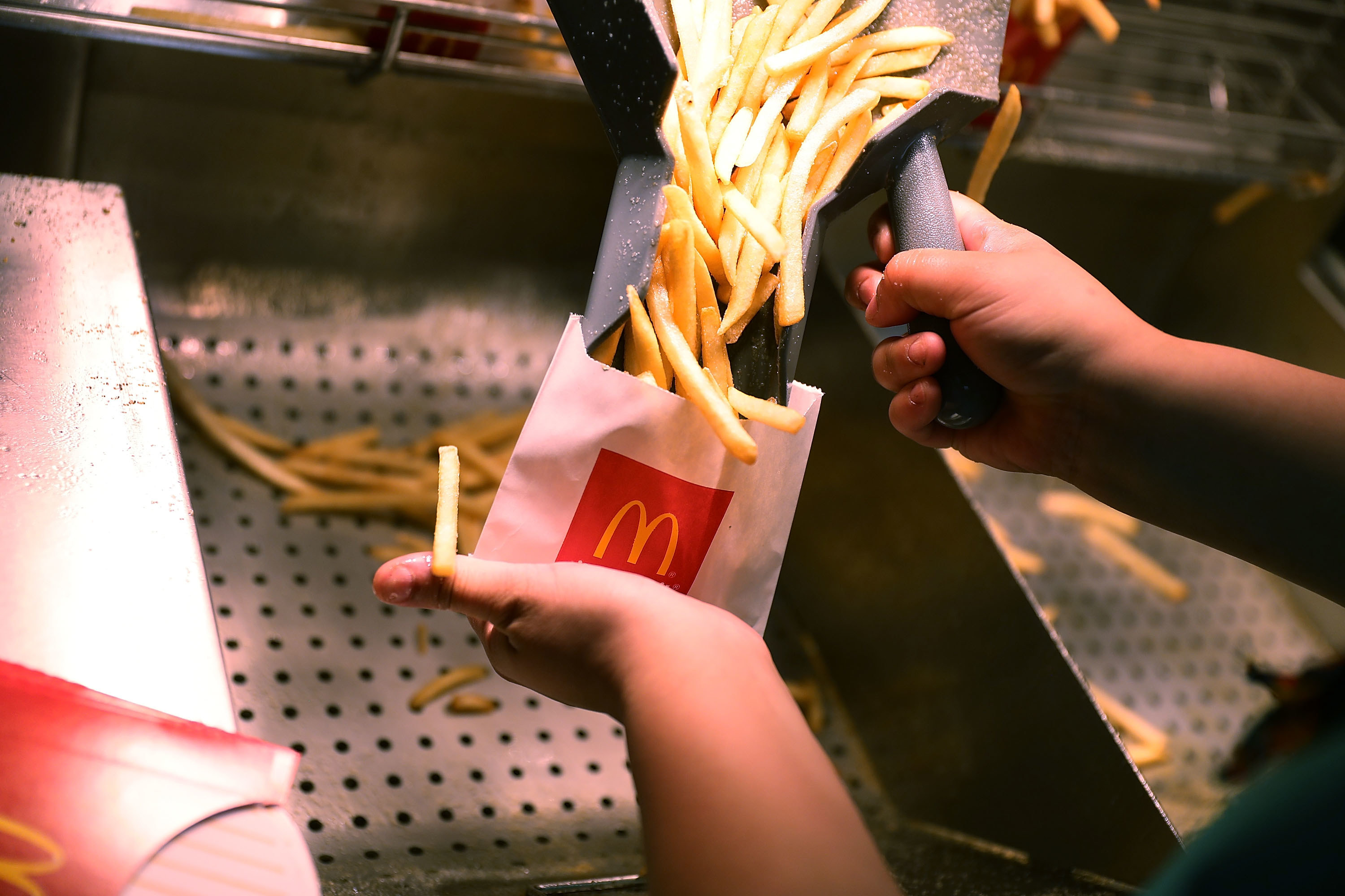 Person putting fries into a McDonald's packet