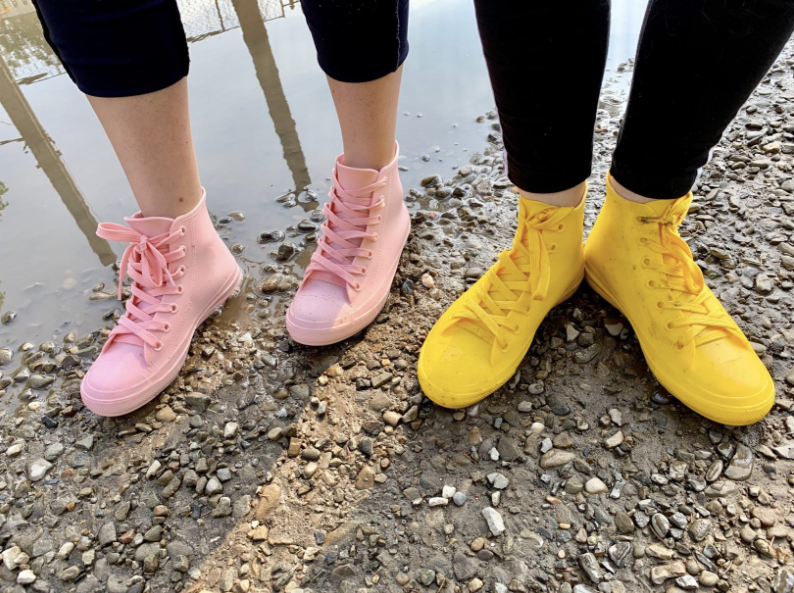 two reviewers wearing high-top sneaker style rain shoes in light blue and yellow