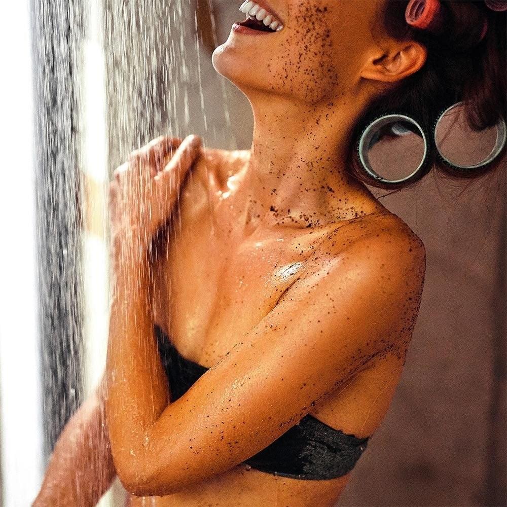 model applying scrub all over body