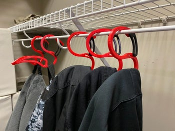 Five hoodie hangers hanging in a closet with hoodies on them