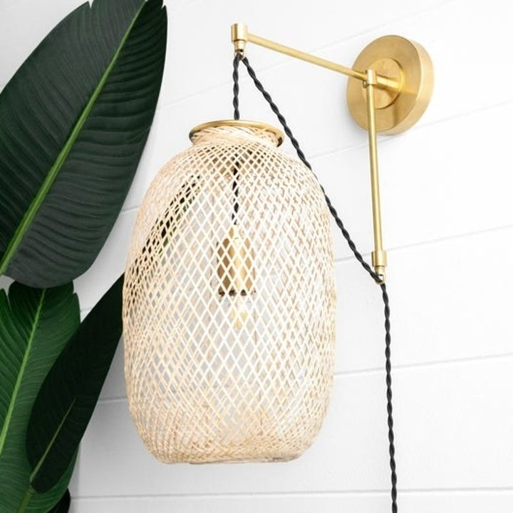 the same sconce with a brass-tone bracket and a wire basket shade