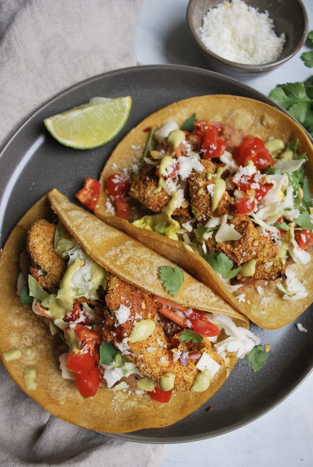 """Two tacos filled with avocado """"fries"""", slaw, and veggies."""