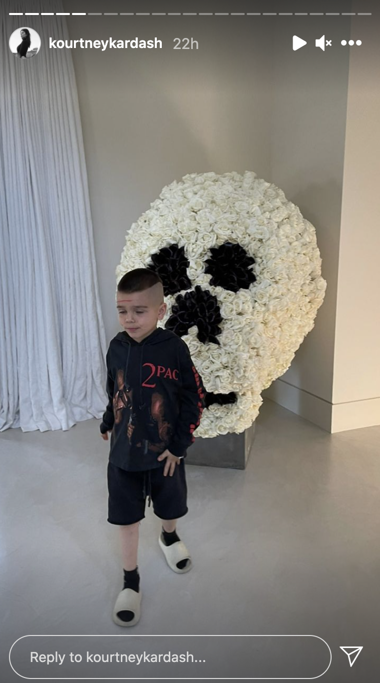 Reign standing in front of the flower arrangement