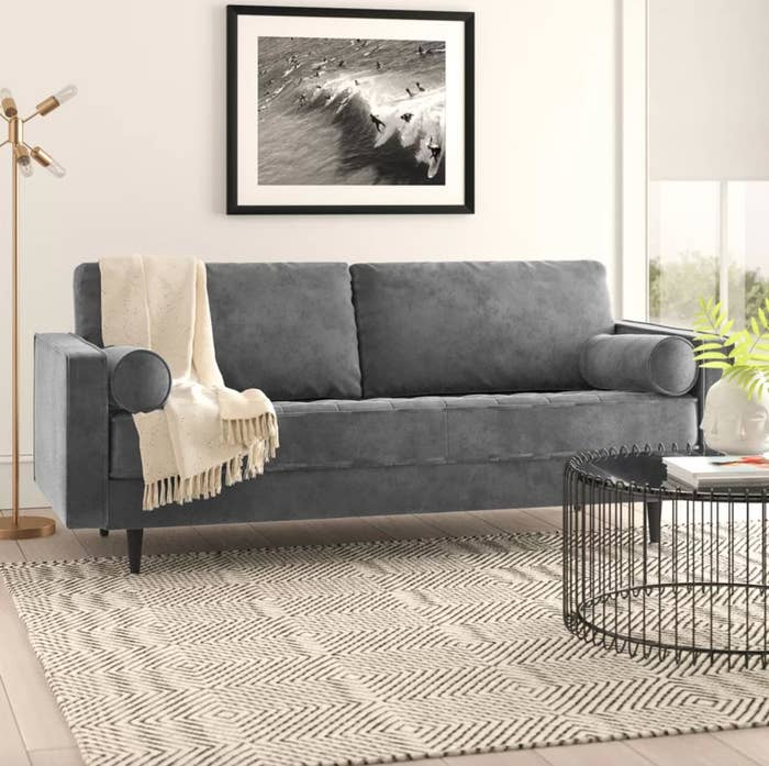 The square arm sofa in charcoal gray fabric with a beige blanket drapped over it