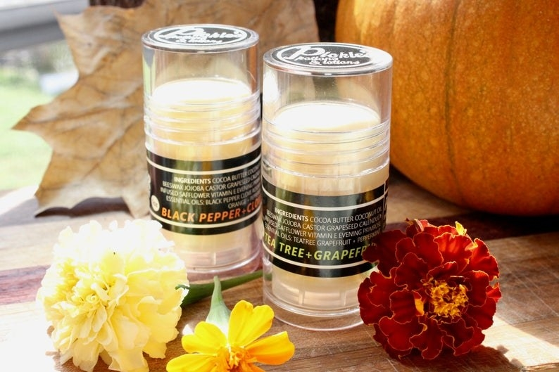 Two large tubes of the balm in the black pepper and clove and tea tree and grapefruit versions