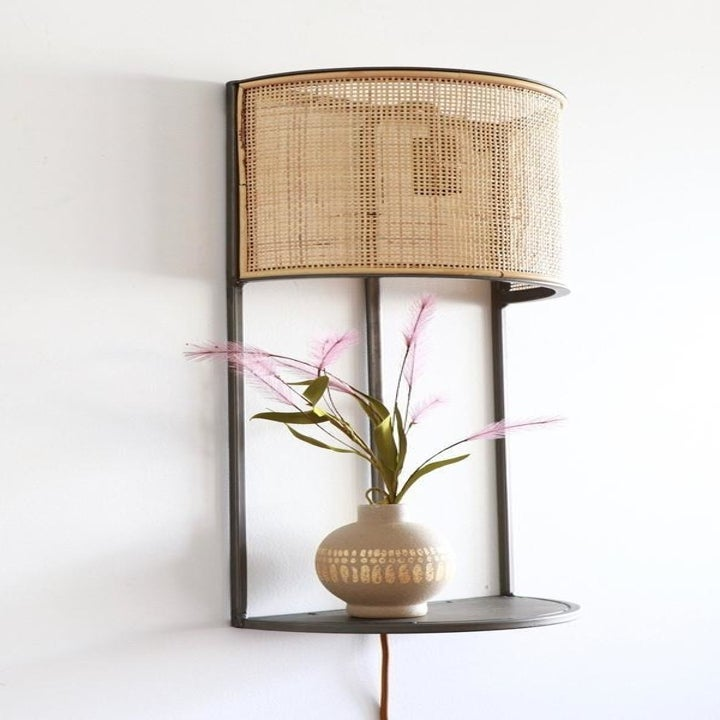 the lamp with a rattan shade and built-in metal shelf with a plant sitting on it and a cord hanging down