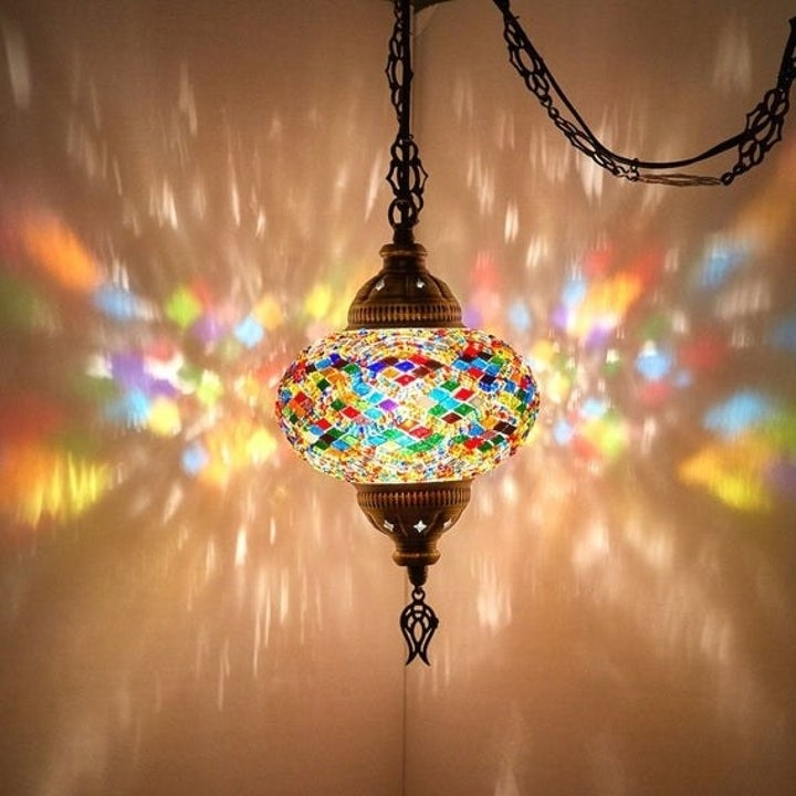 a hanging glass lamp with multicolored glass shining colorful patterns on the surrounding walls s