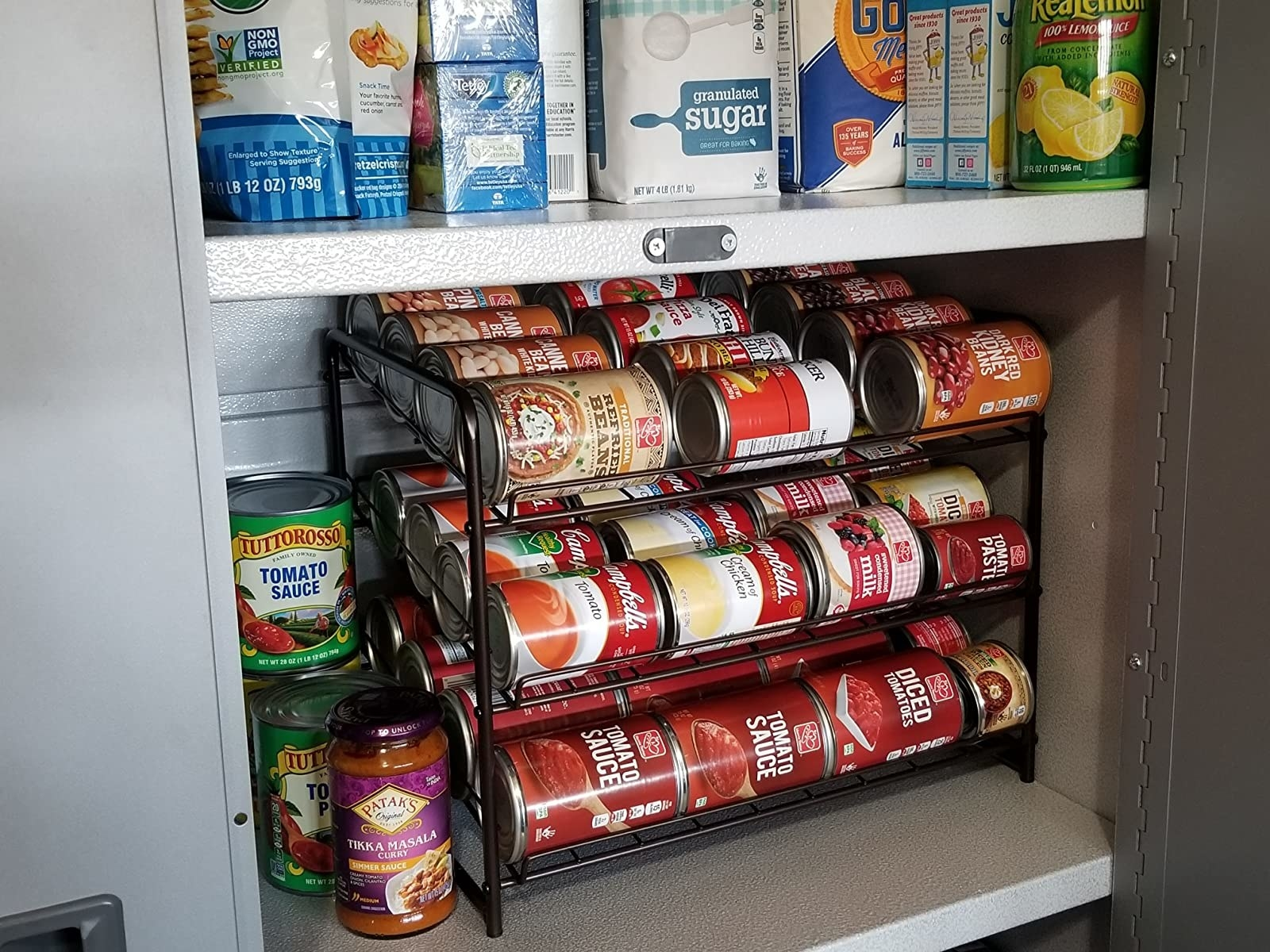 Review image showing the can organizer in their pantry filled with cans