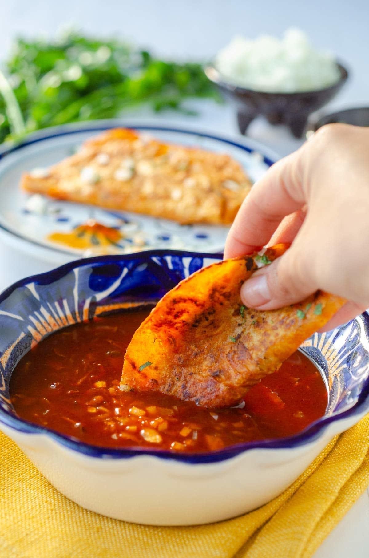 A vegan birria taco being dipped in broth.