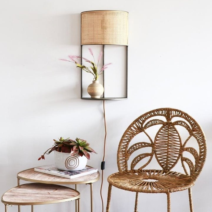 a chair and side tables with the lamp and built-in shelf hanging on the wall above