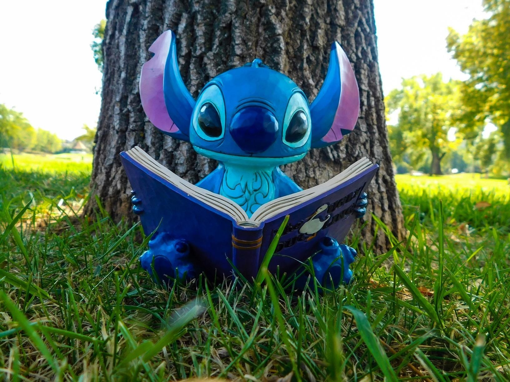 a figure of stitch reading the ugly duckling book