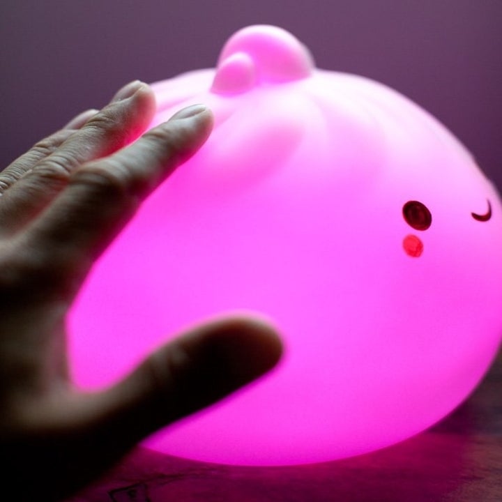 a hand touching the lamp that's emitting pink light
