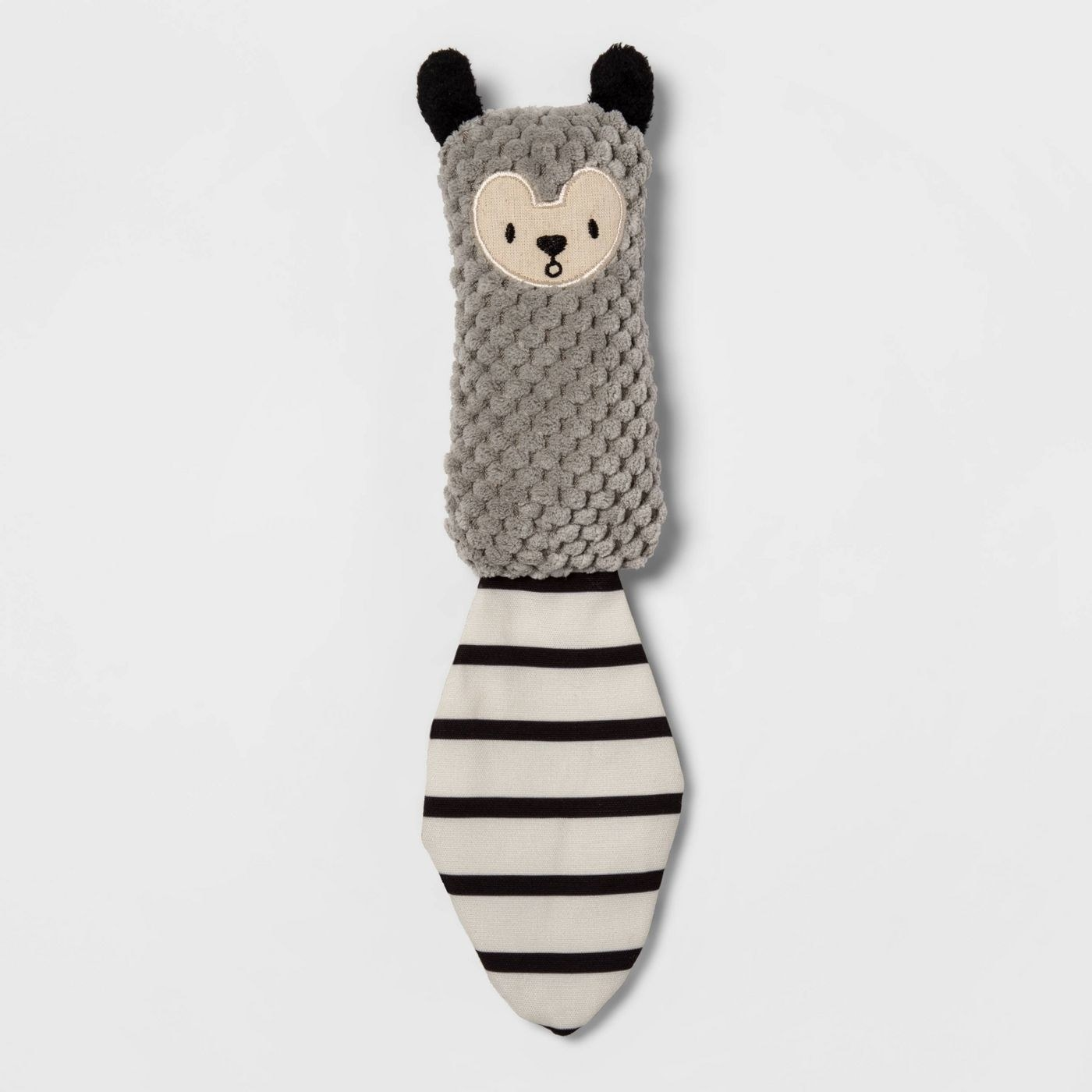 The soft gray toy, which has a white tail with black strips