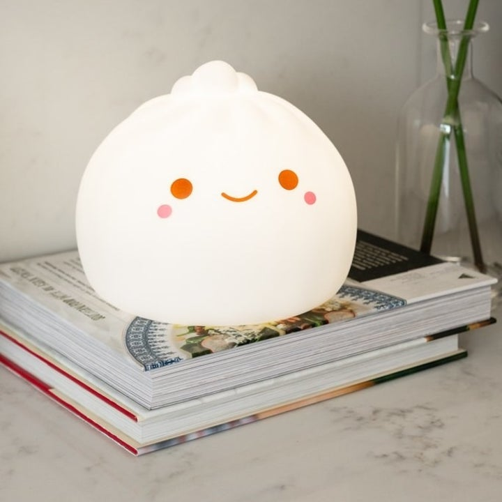 a dumpling-shaped lamp with a face sitting on a stack of magazines
