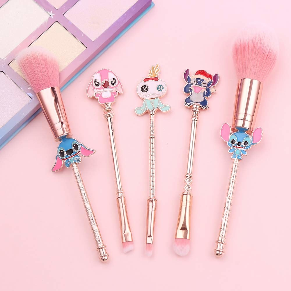 makeup brushes with stitch, angel, and scrump charms on them