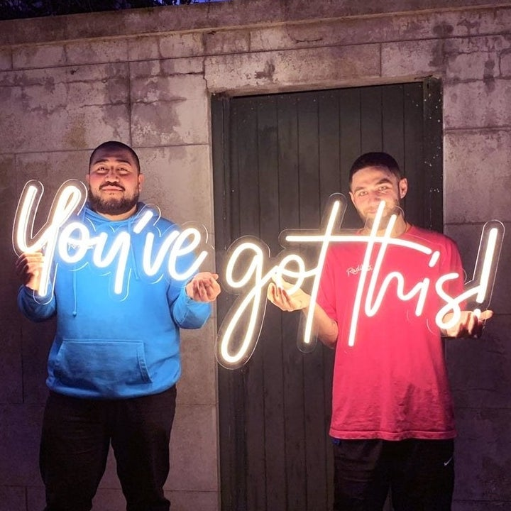 """Two models holding a white neon sign that says """"you got this!"""""""