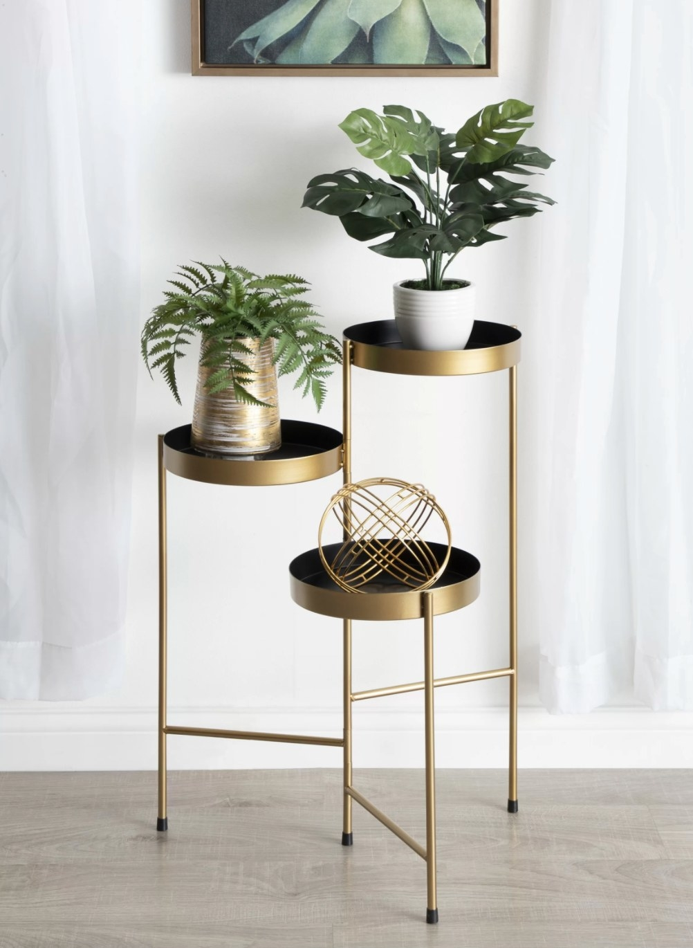 The round multi-tiered plant stand in gold and black holding multiple plants