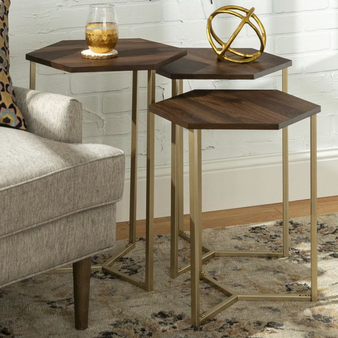The set of three nesting tables in dark wood and gold holding a glass of water
