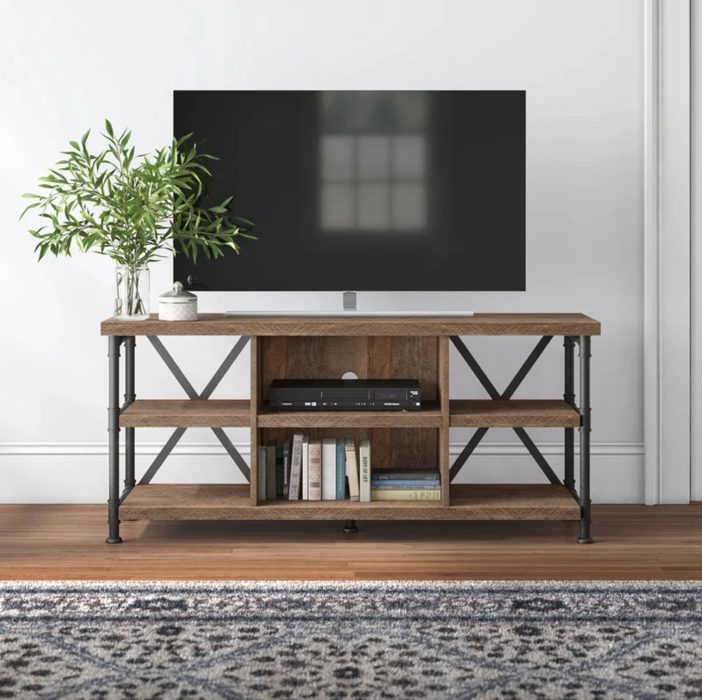The wood TV stand with metal legs holding a flat-screen TV and a vase of flowers