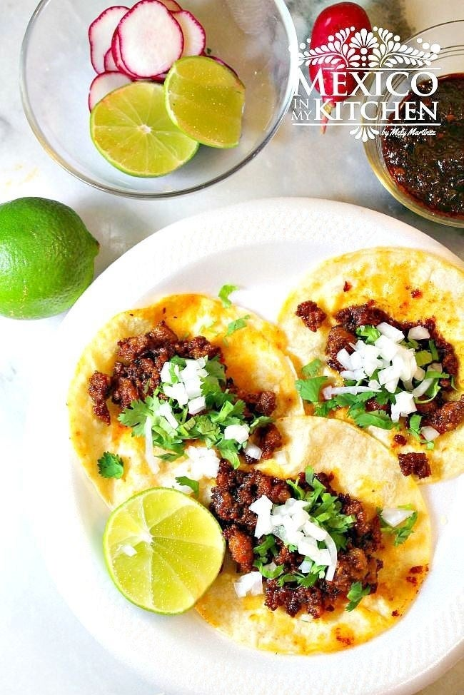 Three chorizo tacos topped with onion and cilantro.
