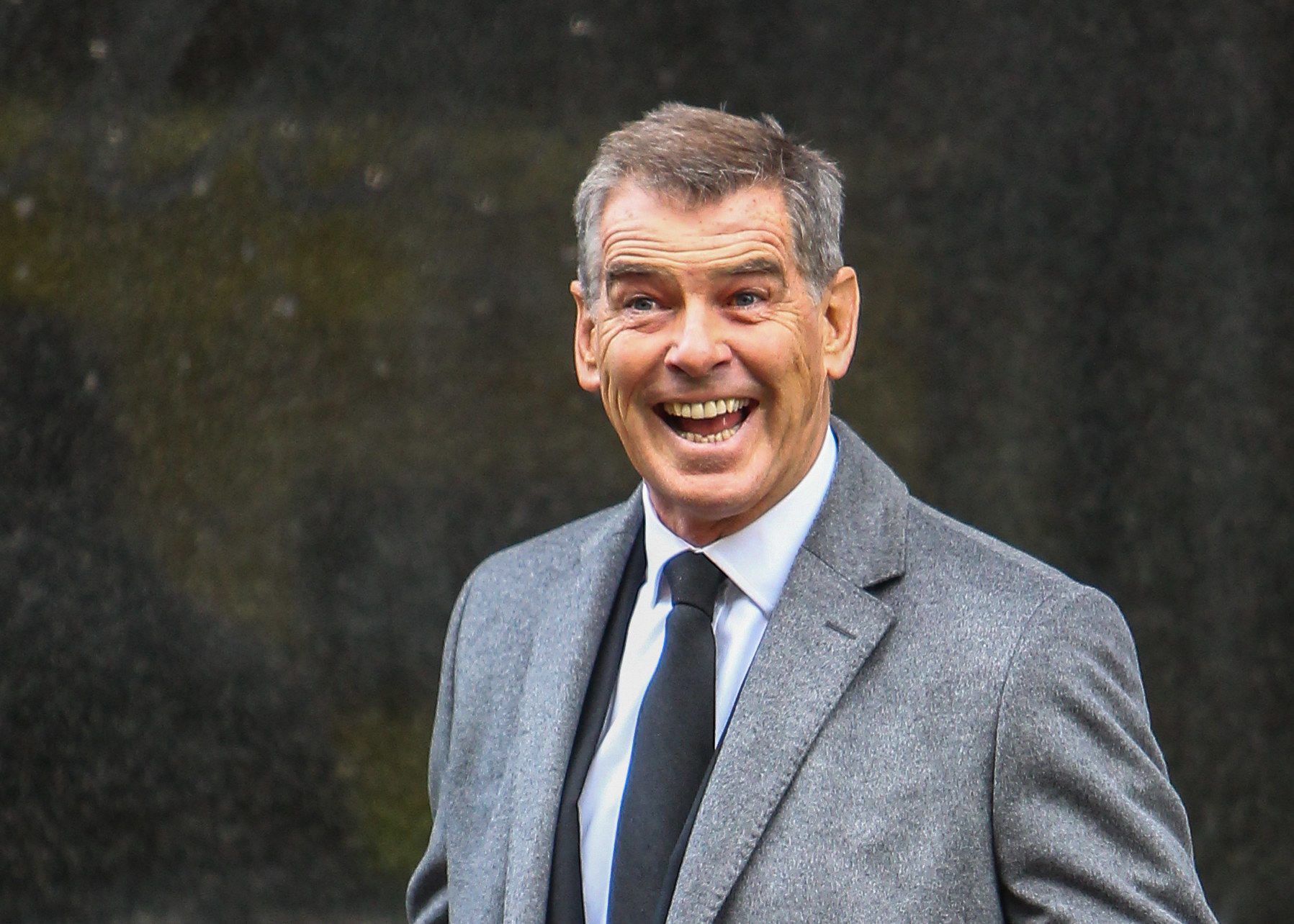 Pierce Brosnan smiling widely.