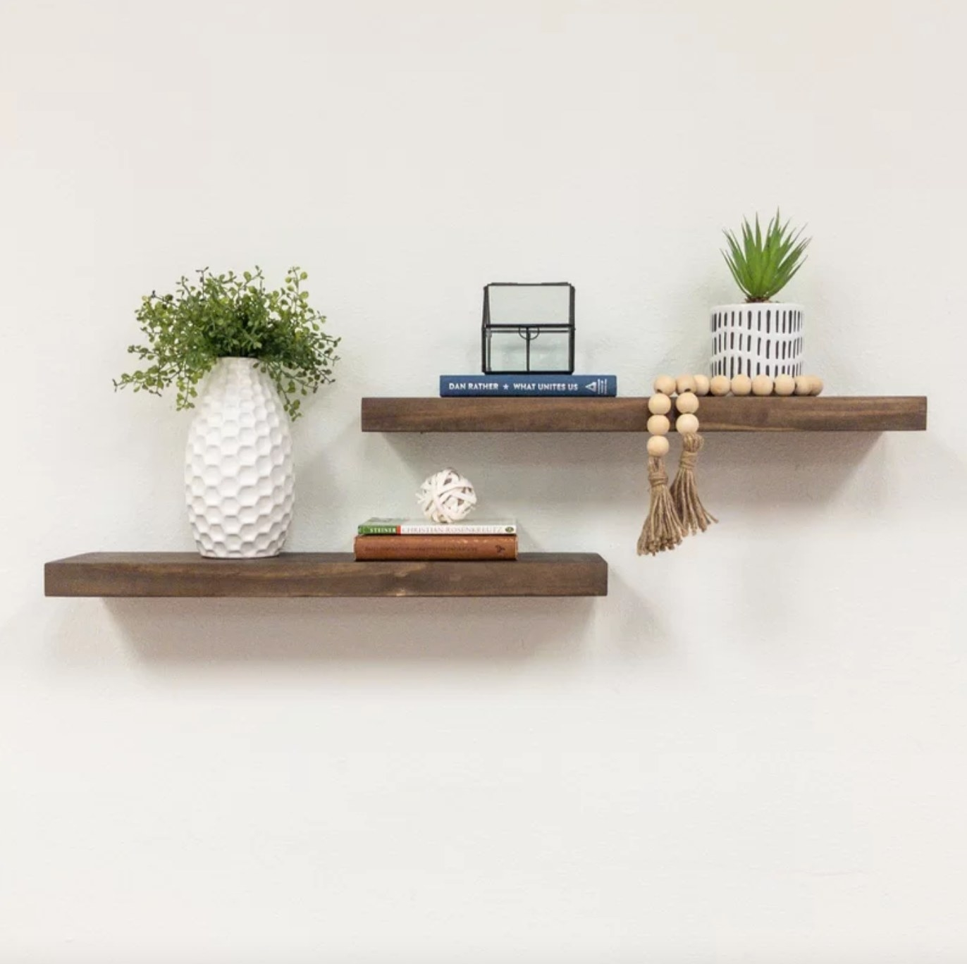 The set of two pine wood floating shelves in dark walnut holding plants, books, and trinkets