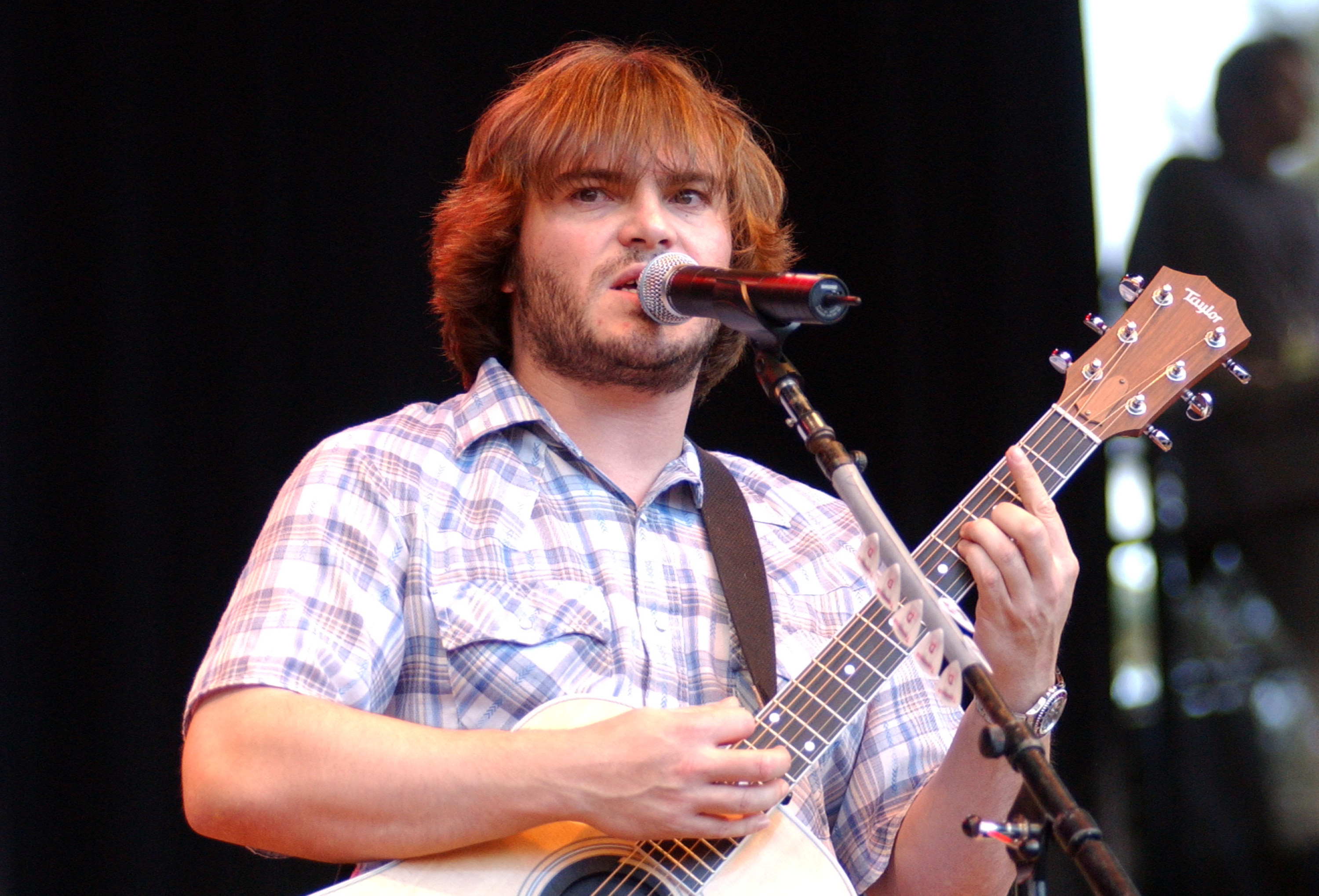 Jack Black performing on stage with a guitar