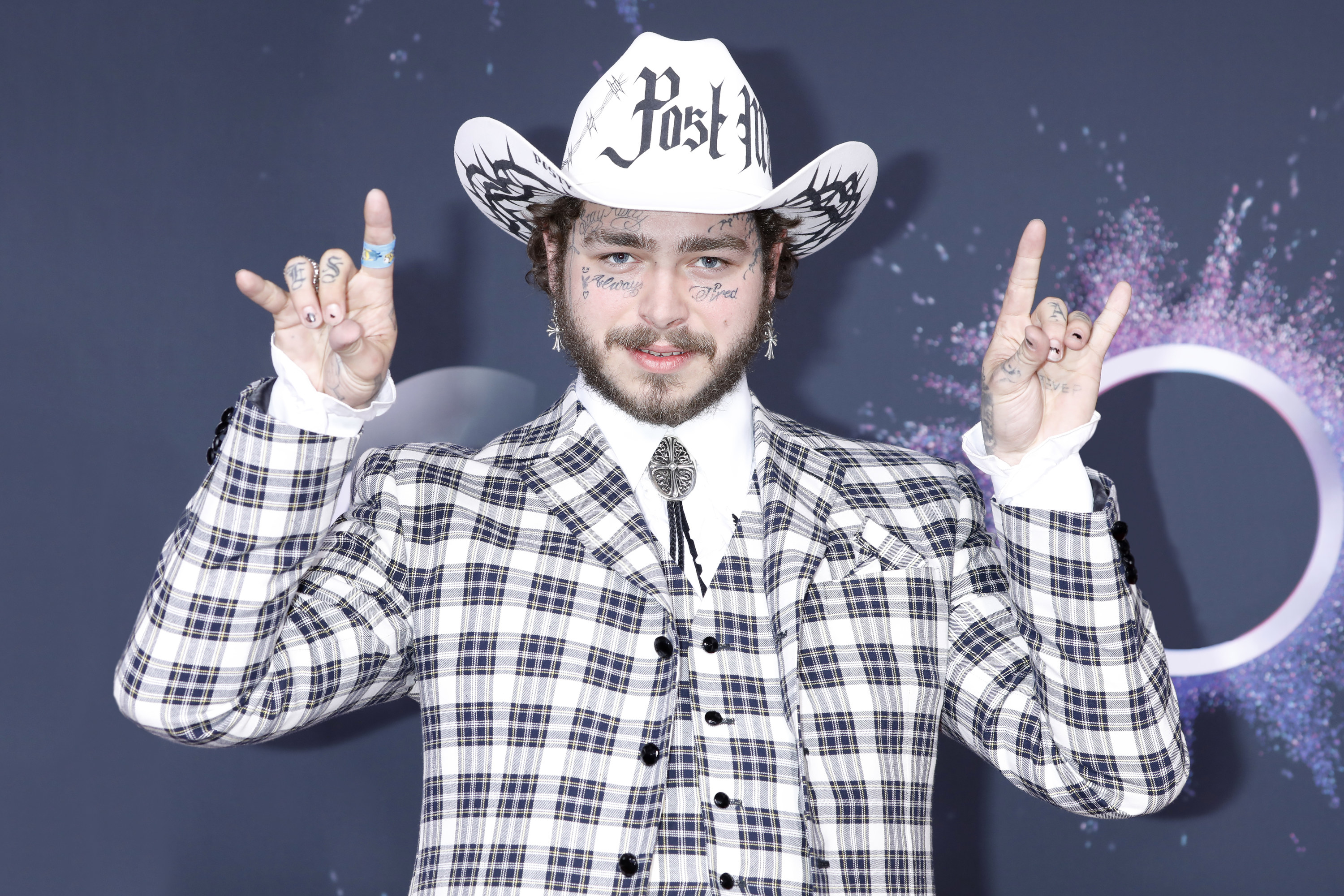Post Malone in a plaid suit and cowboy hat