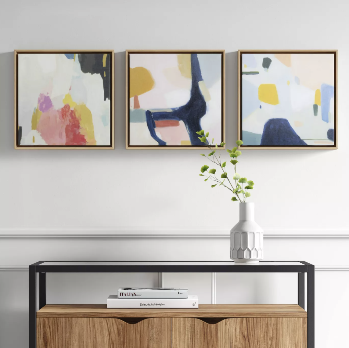 three modern canvases hung over a console table
