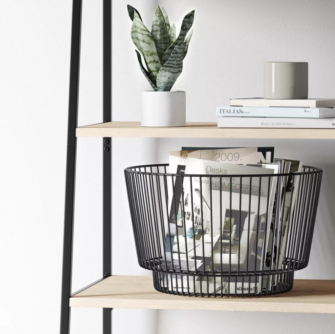 the black storage basket holding magazines