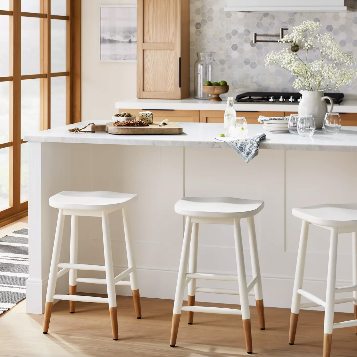 three white and brown bar stool pulled up to an island