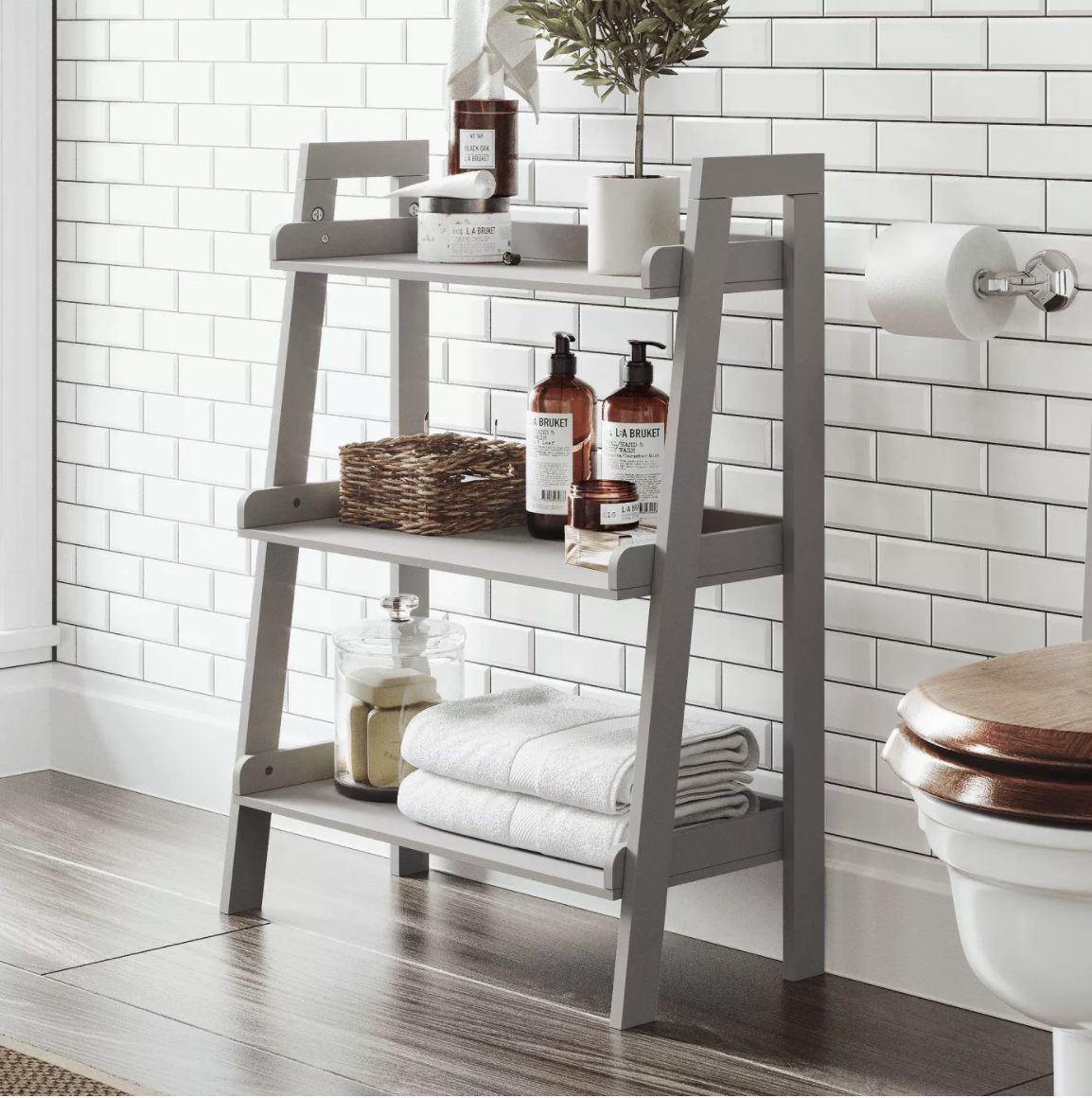 the grey three-tier storage unit holding towels and toiletries