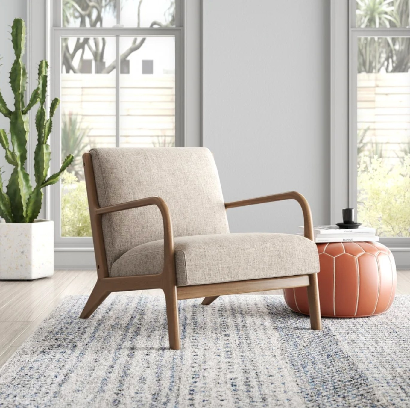 The midcentury armchair in taupe next to an orange pouf