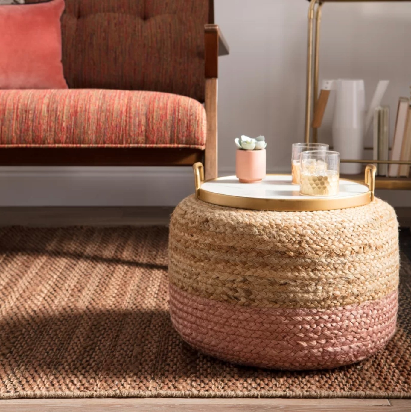 The round pouf ottoman in beige/ light pink holding a tray of drinks