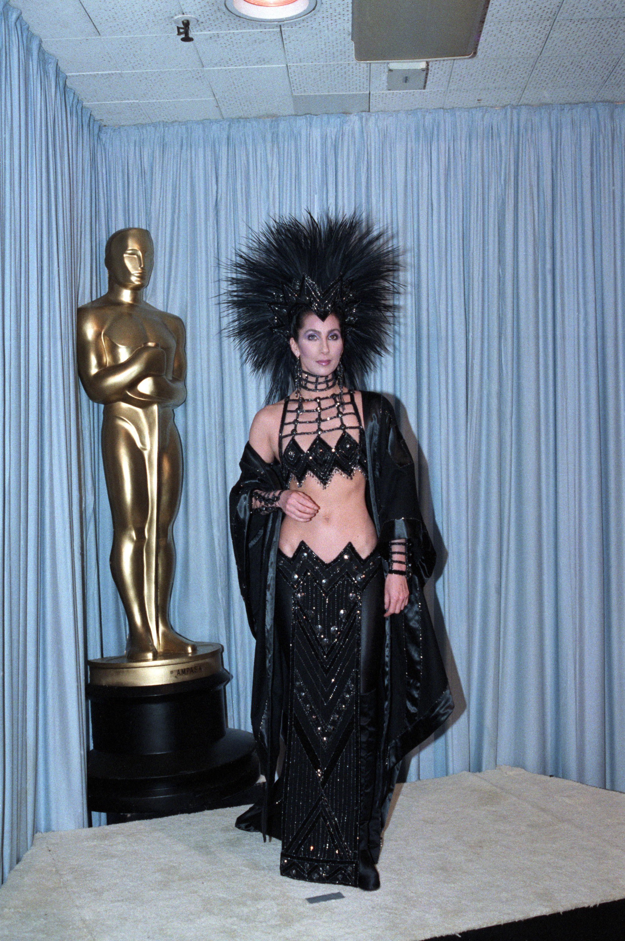 Cher dressed in a midriff-baring long black gown with a plumed headpiece