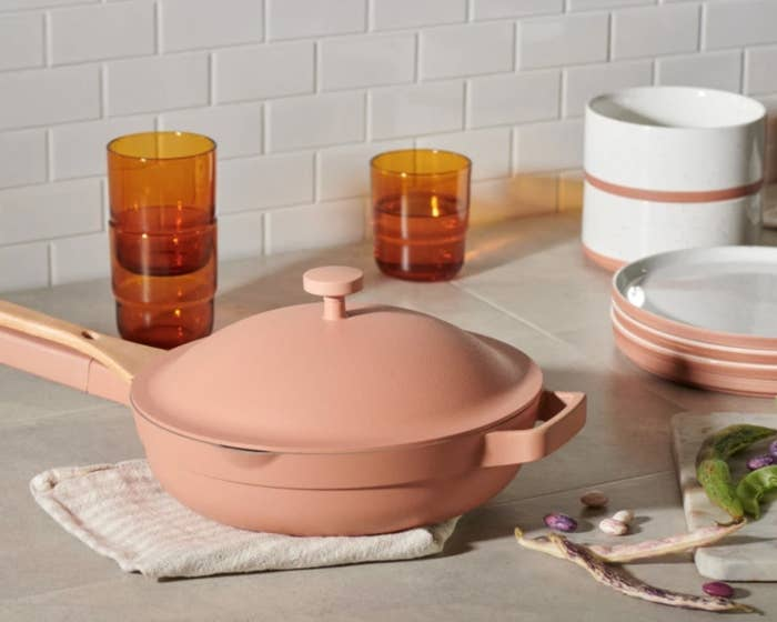 The deep skillet-like pan in a pinkish color with a full matching lid, and a bamboo stirrer attached to the handle