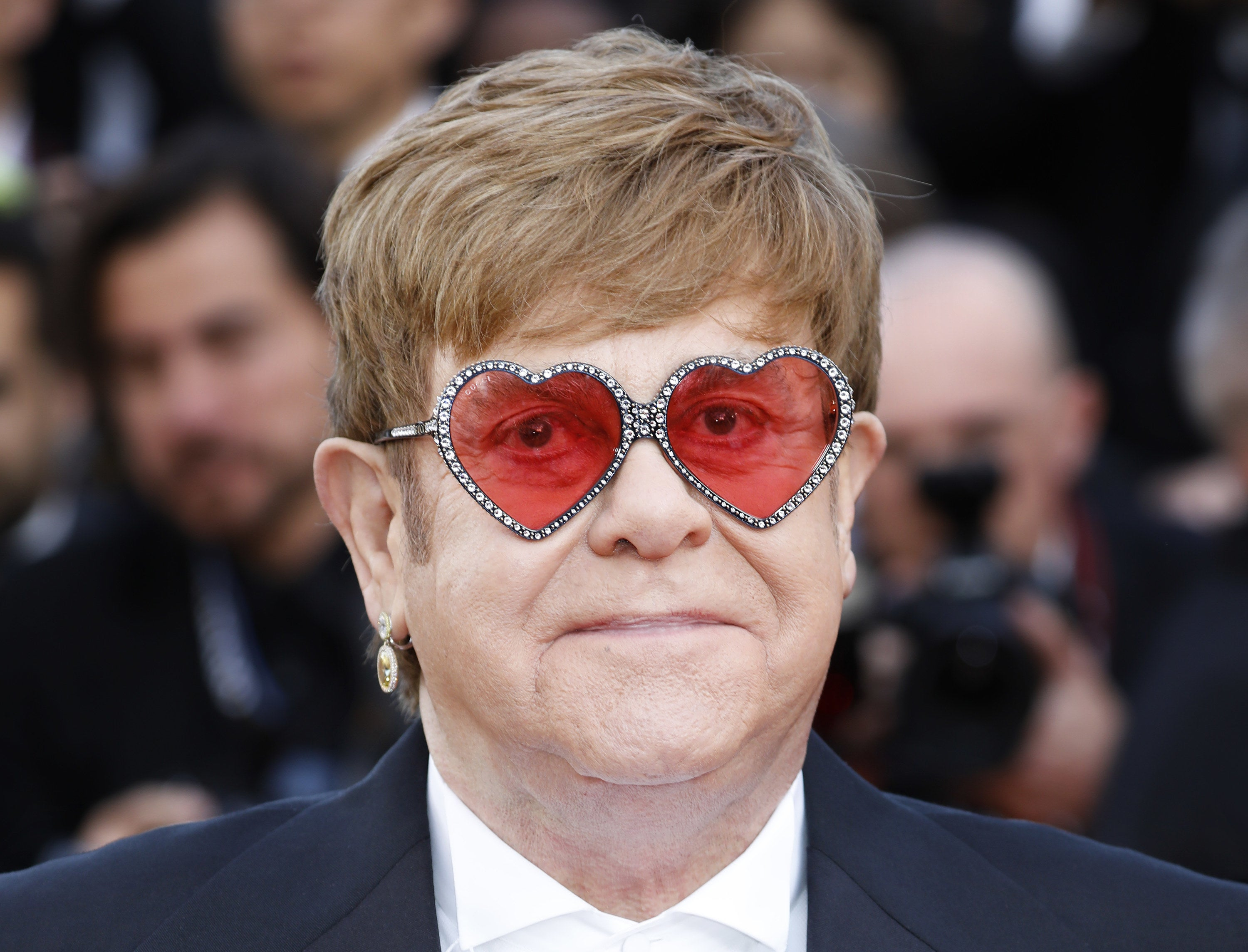 Photo of Elton John in heart-shaped sunglasses and a suit
