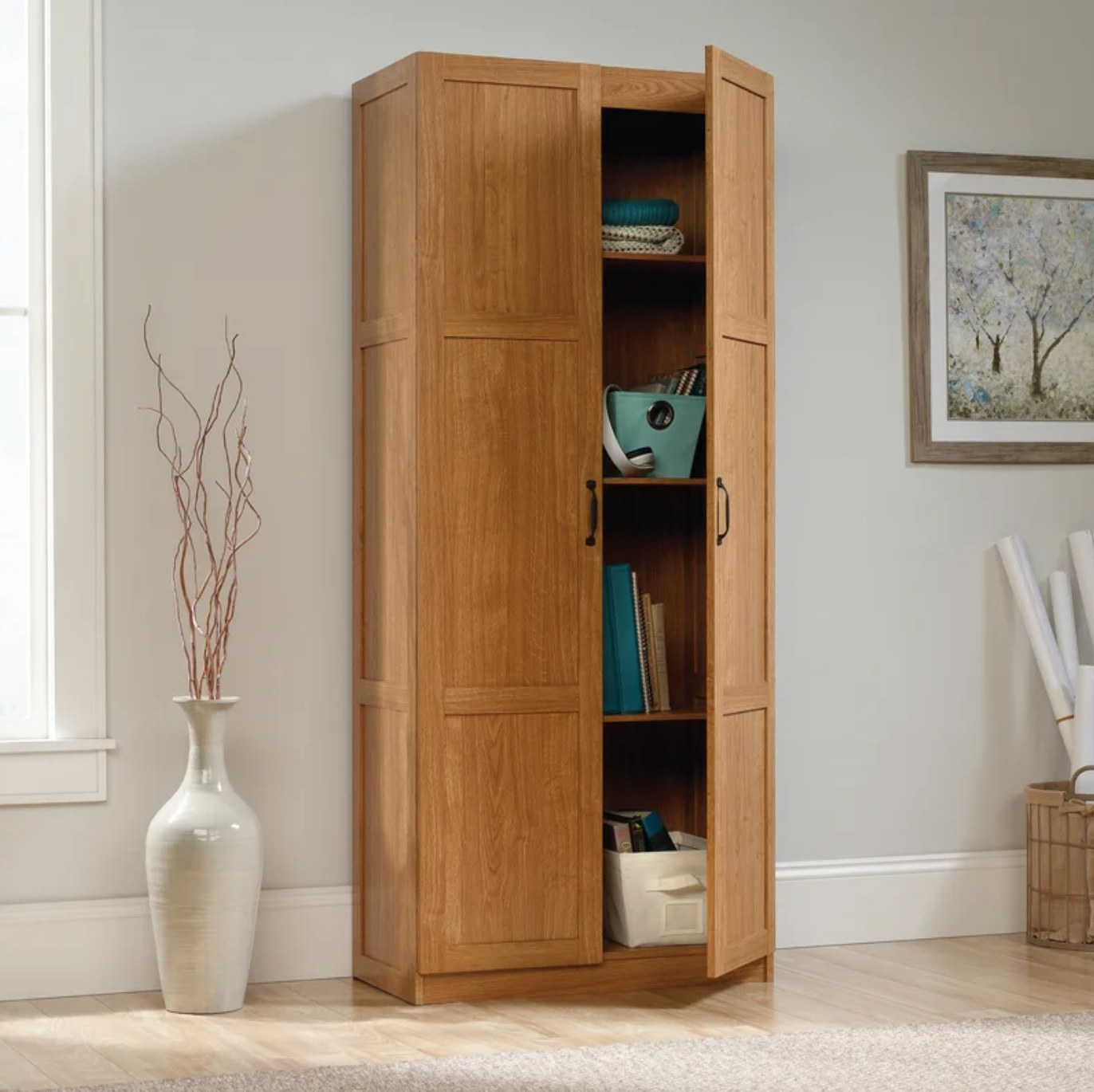 The armoire in highland oak holding books and other essentials