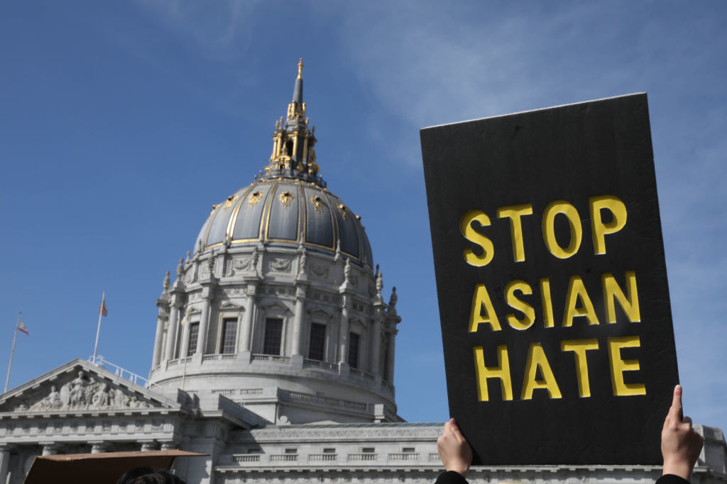 """person holding a """"stop asian hate"""" sign"""