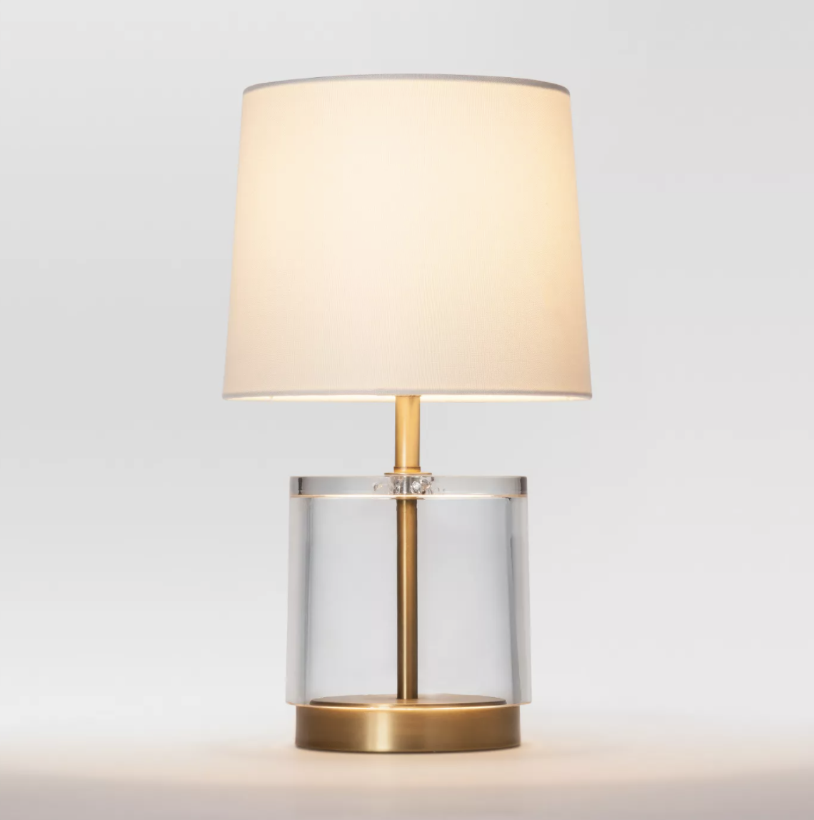 the acrylic and brass table lamp with a beige lampshade