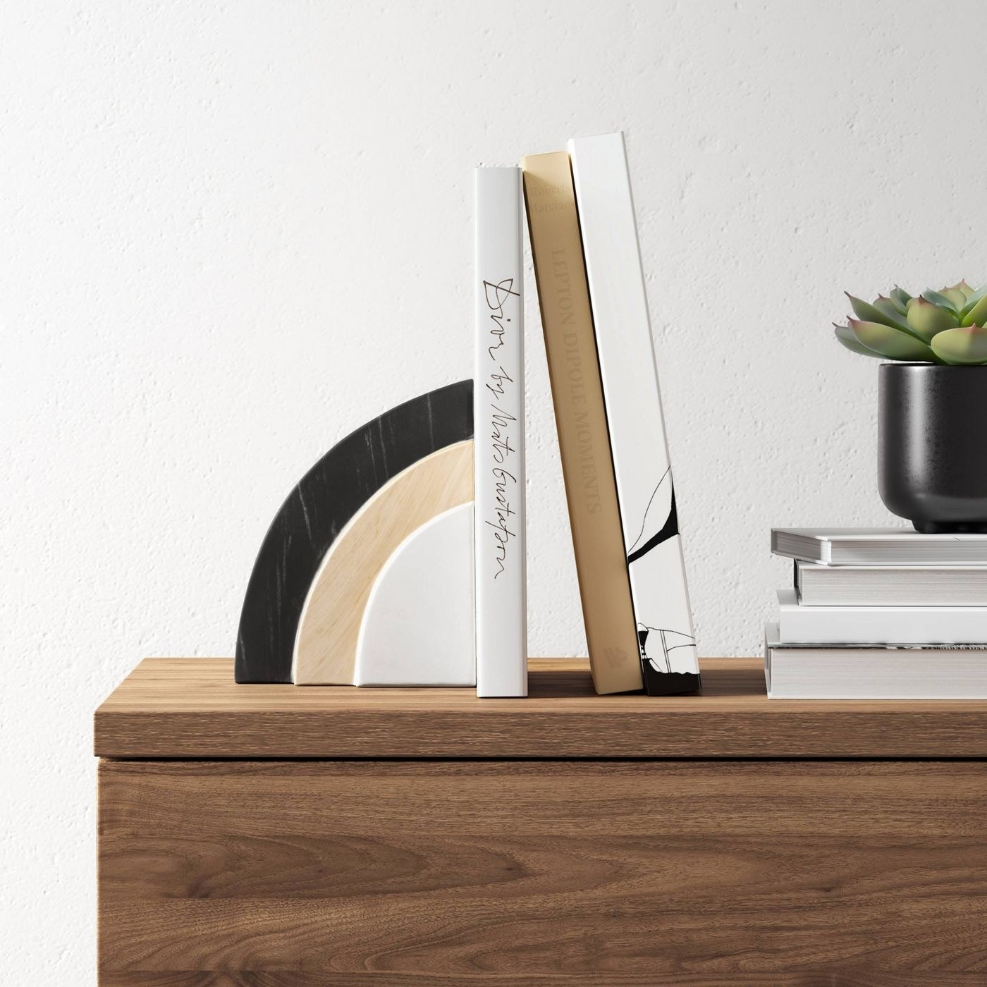 rounded book end with a layer of white, layer of light tan, and a layer of black holding up some books