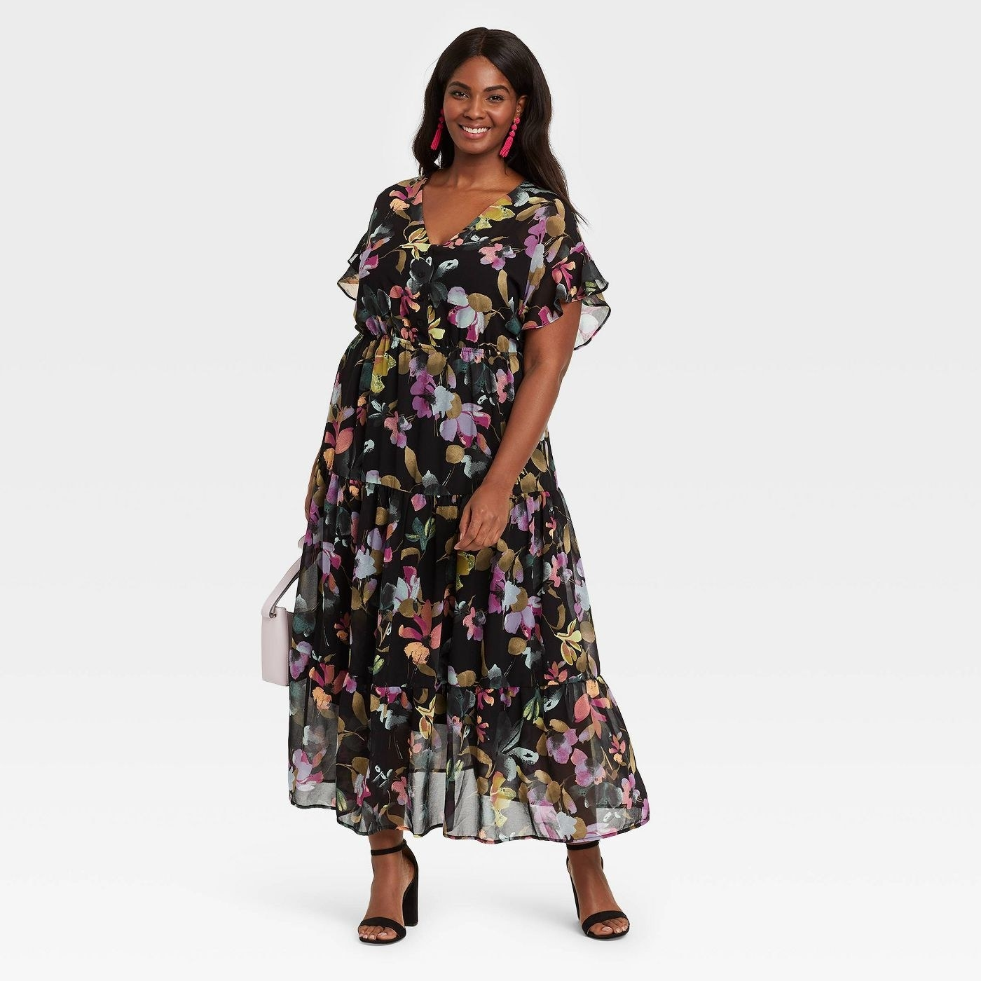 model wearing the tiered black maxi dress with gold, pink, and orange flowers all over it