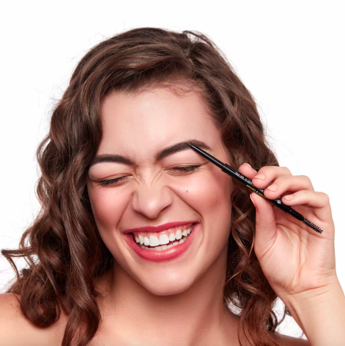 A model apply the pencil to her eyebrows