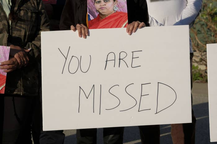 """Someone holds up a sign that reads """"you are missed"""""""